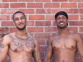 two tattooed latino gays posing exposed outside